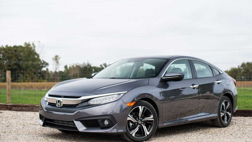 Three quarters view of dark gunmetal grey 2016 Honda Civic on a stone driveway in front of a fenced in field.