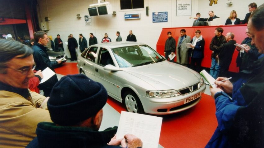 Image of man reviewing vehicle before purchase at a car auction.