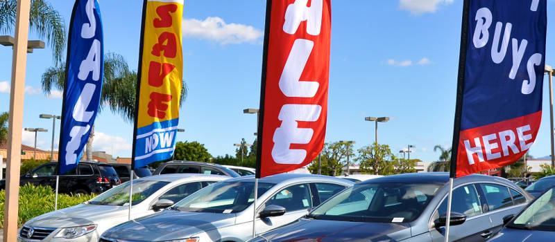 car dealership with sales signs up on a sunny day.